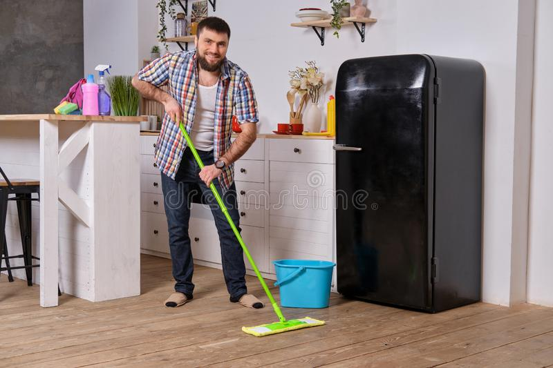 Husband housekeeper cleans the kitchen. Young happy man with green mop washes the floor royalty free stock images