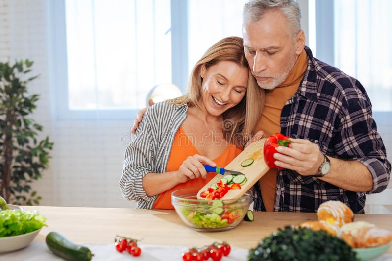 Husband hugging his wife cooking healthy salad for lunch royalty free stock photography