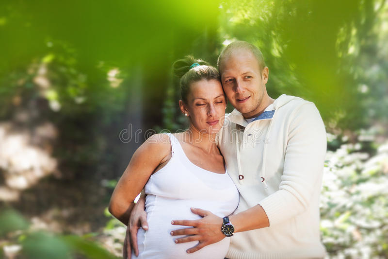 Husband hugging pregnant wife stock photography