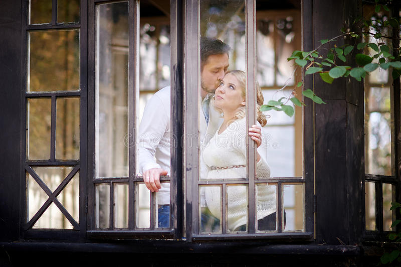 Husband kisses his pregnant wife in the house. View through window stock image