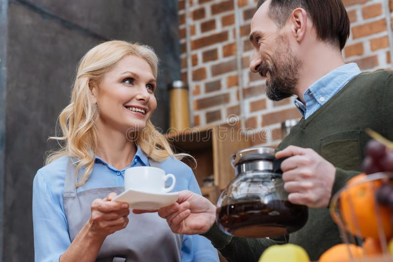Husband proposing coffee to wife. In kitchen stock photos