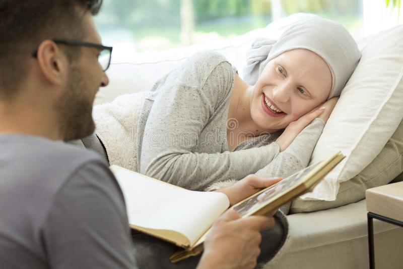 Husband reading a book to a smiling sick woman with headscarf. L stock photo