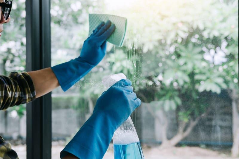 Husband-Reinigungskonzept, Happy junger Mann wischt Staub mit einem Spray und einem Staubfilter bei der Reinigung in Glas zu Haus lizenzfreie stockfotos