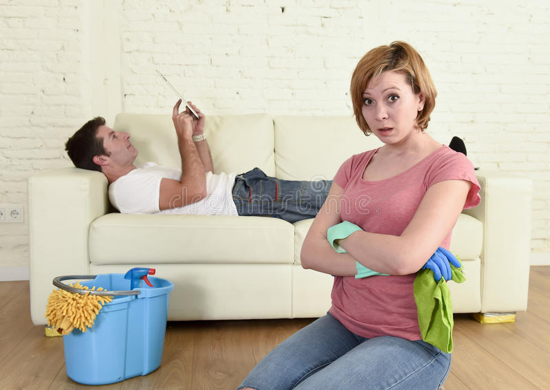 Husband resting on couch while wife cleaning doing housework in chauvinism concept. Young couple with women or wife kneeling washing and cleaning the floor royalty free stock image