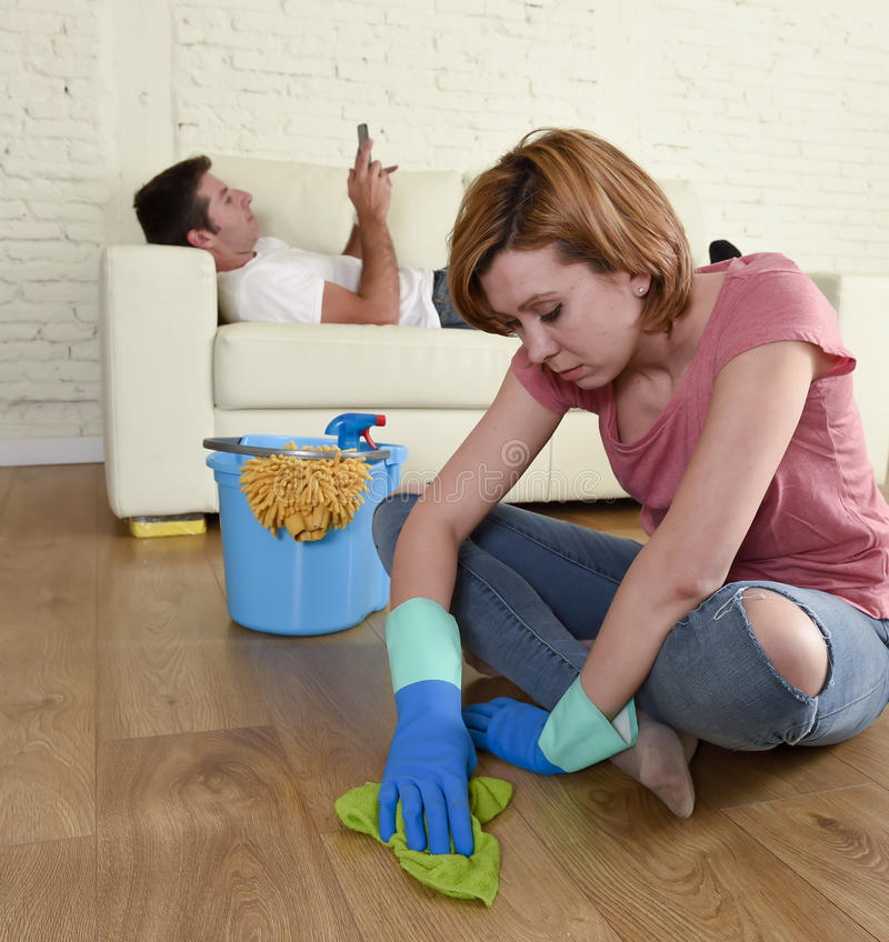 Husband resting on couch while wife cleaning doing housework in chauvinism concept. Young couple with women or wife kneeling washing and cleaning the floor stock image