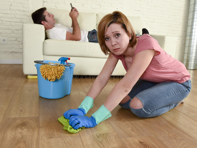 Husband resting on couch while wife cleaning doing housework in chauvinism concept. Young couple with women or wife kneeling washing and cleaning the floor stock photo
