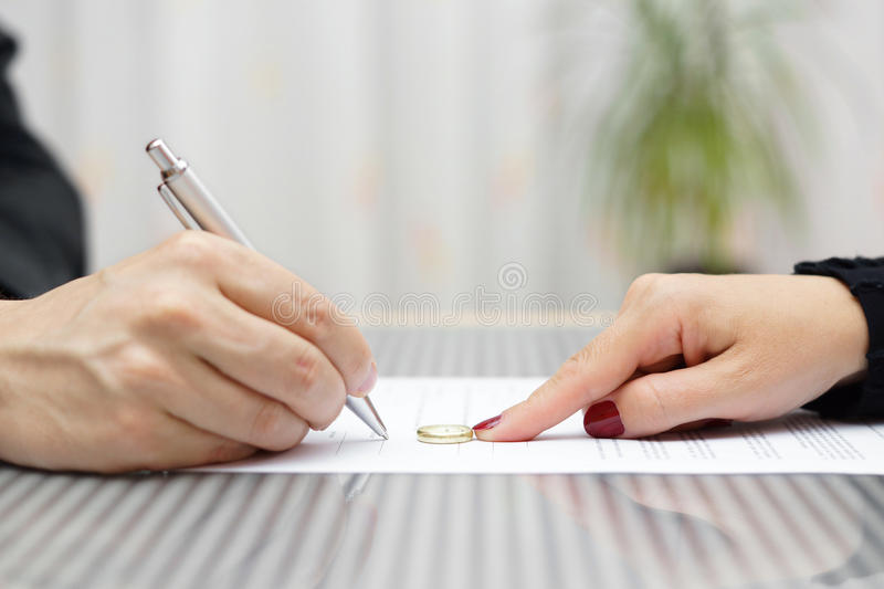 Husband signing divorce agreement and woman push away ring. Husband signing divorce agreement and woman push away weeding ring royalty free stock photography
