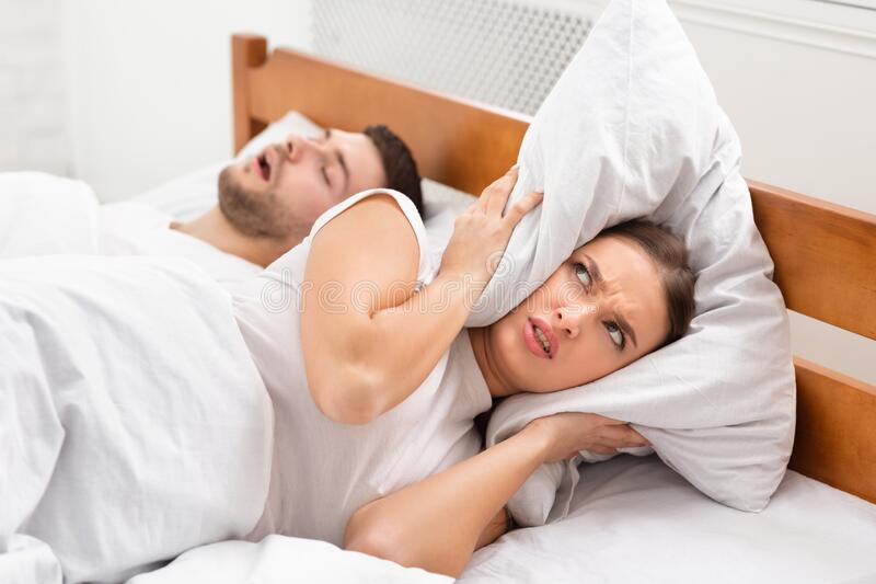 Husband Snoring Bothering Angry Wife Lying In Bed Indoor. Husband Snoring Bothering Angry Wife Unable To Get To Sleep Covering Ears With Pillow Lying In Bed royalty free stock photos