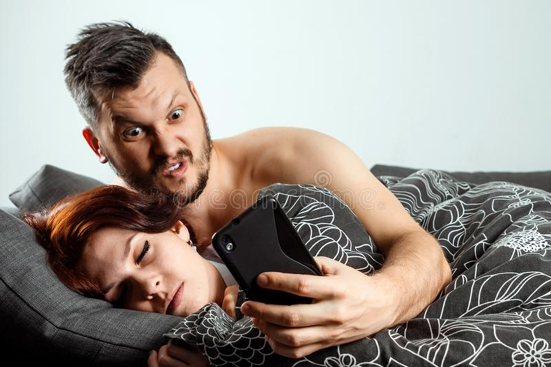 Husband spies on his wife`s phone while she sleeps. The concept of distrust, betrayal, jealousy, relationships, problems.  royalty free stock photos