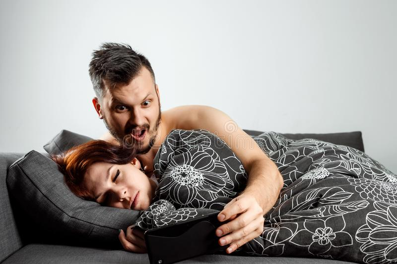Husband spies on his wife`s phone while she sleeps. The concept of distrust, betrayal, jealousy, relationships, problems.  stock image