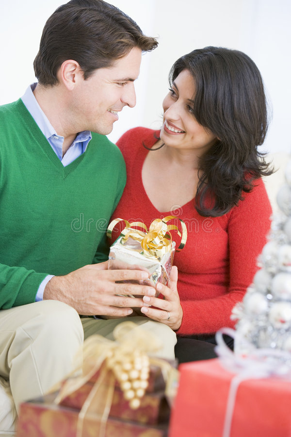 Husband Surprising Wife With Christmas Present stock photos
