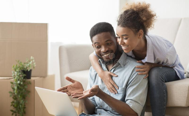 Husband Using Laptop Showing Something Wife Sitting On Couch Indoor. Relocation. Smiling Black Husband Using Laptop Showing Something His Wife Sitting On Couch royalty free stock photos