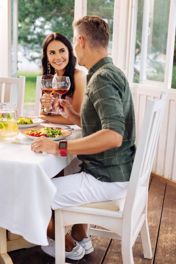 Husband wearing smart watch drinking wine with beautiful wife stock photography