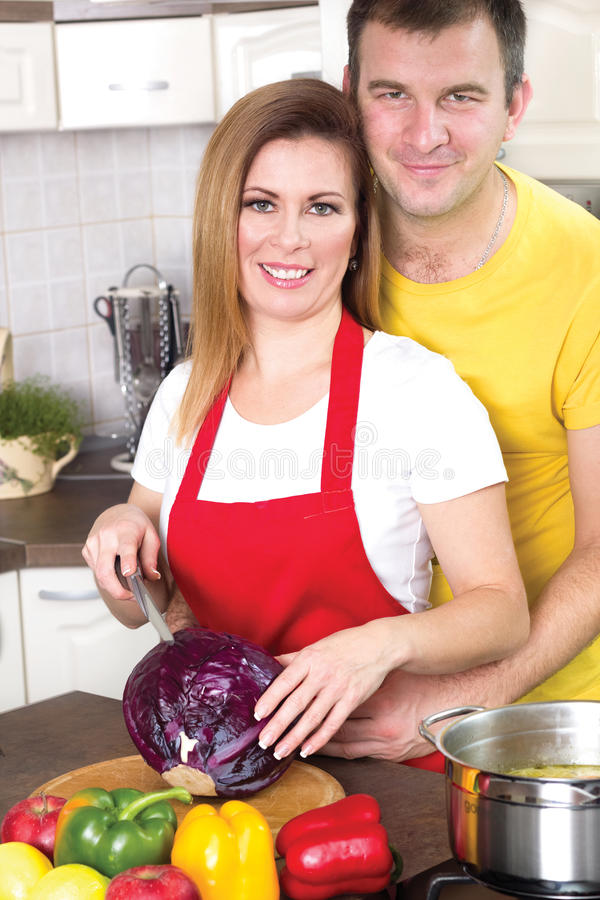 Husband and wife cooking together in the kitchen at home