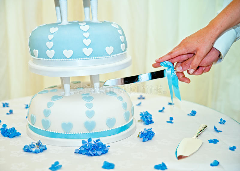 Husband and wife cutting weedding cake stock images