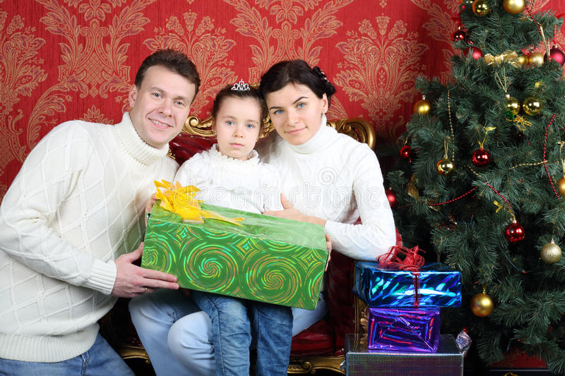 Husband, wife and daugther with gift smile near Christmas tree. In red room royalty free stock photos