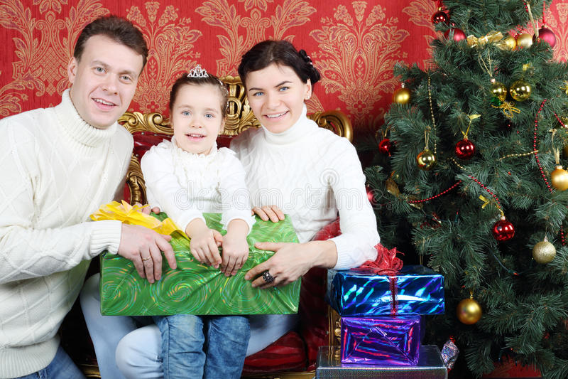 Husband, wife and daugther hold gift and smile. Near Christmas tree at home royalty free stock image