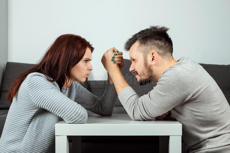 Husband and wife are fighting in their arms, arm wrestling between male and female. Family quarrel, showdown, division of property. Divorce. The struggle stock photography