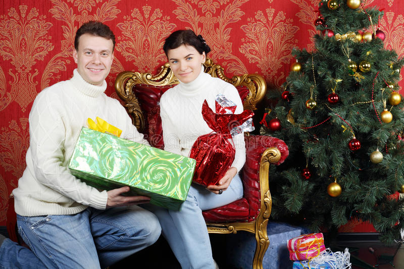Husband and wife with gifts smile near Christmas tree. In red room royalty free stock images
