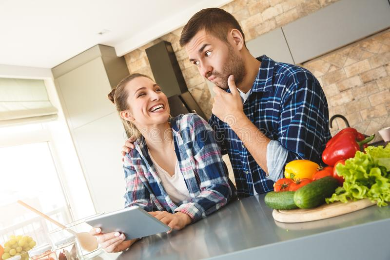 Young couple at home standing in kitchen together concerned husband hugging wife playing game on digital tablet joyful royalty free stock photos