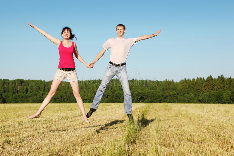 Download Husband, Wife In Jump In Field Stock Photo - Image: 27108198