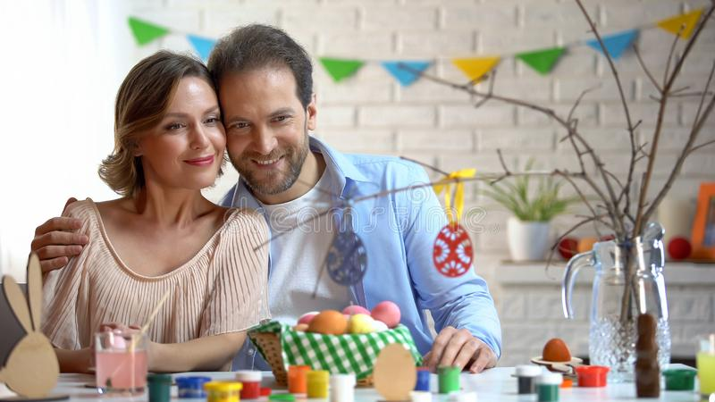 Husband and wife looking at toy eggs on tree-branch, preparing Easter decoration royalty free stock photos