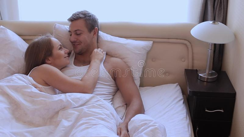 . Husband and wife lying in bed in an embrace  Lifestyle  caucasian