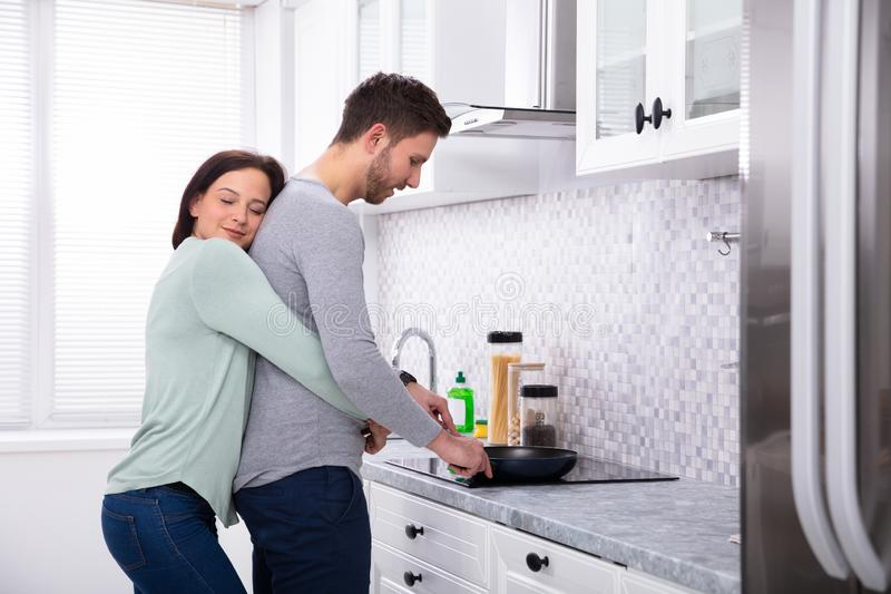Husband And Wife Making Food In Kitchen. Young Husband Making Food With His Smiling Wife Standing In Kitchen royalty free stock photography