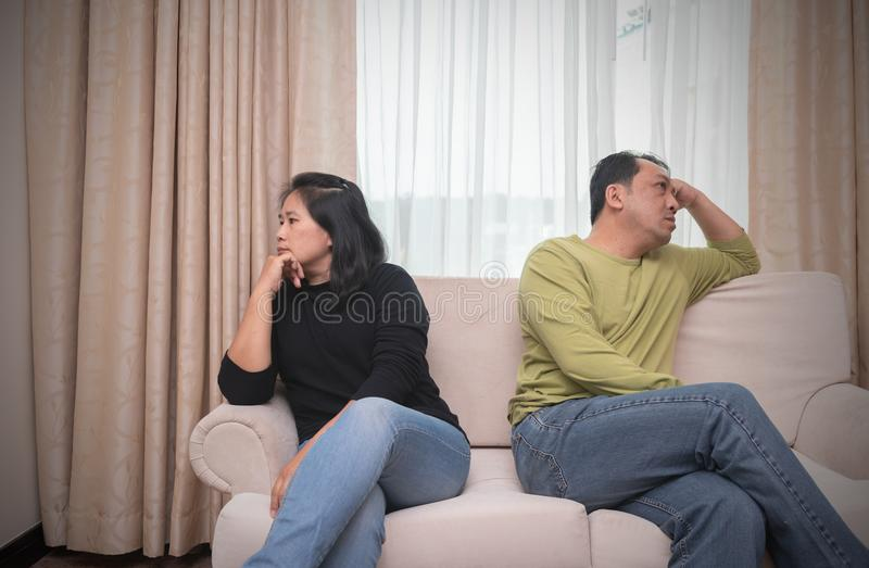 Husband and wife sitting on different sides of sofa. quarrel con stock photos