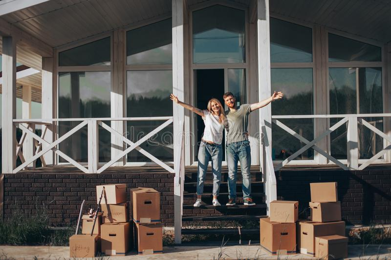 Husband and wife standing in front of new buying home with boxes. Couple Standing on steps on new Home with moving cardboard boxes stock photo