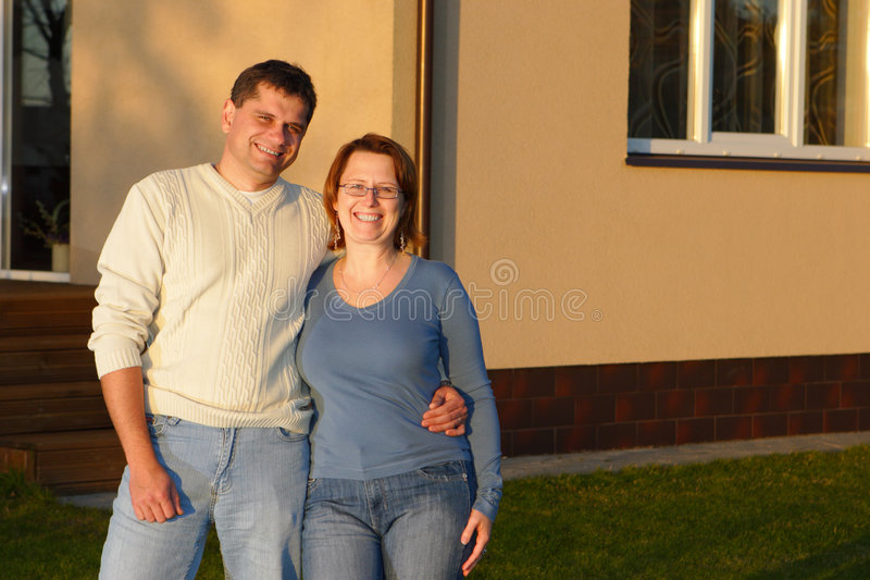 Husband and wife standing near house royalty free stock photos