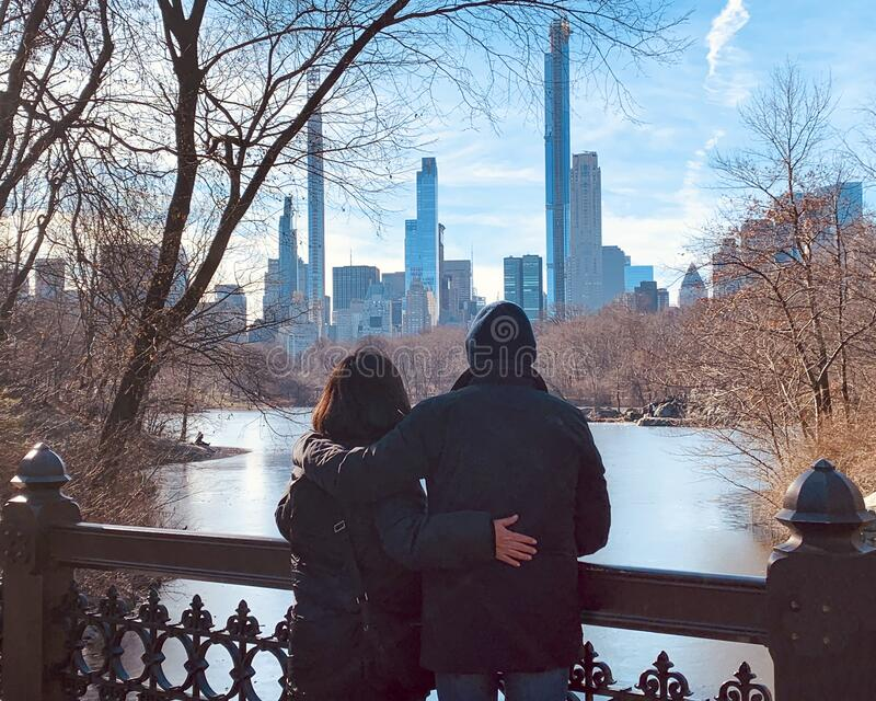 Husband and wife standing on the Old Bridge viewing the skyline of New York City across the Bank Rock Bay. royalty free stock image