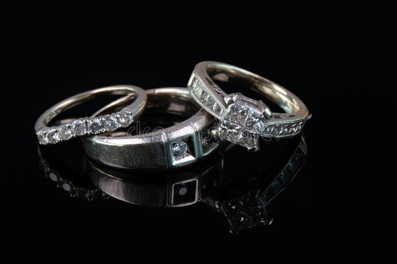 Husband and wife wedding rings on black stock images