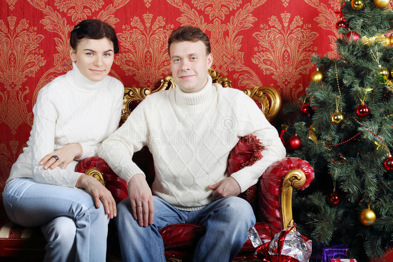 Husband and wife in white sweaters and jeans near Christmas tree. In red room stock photography