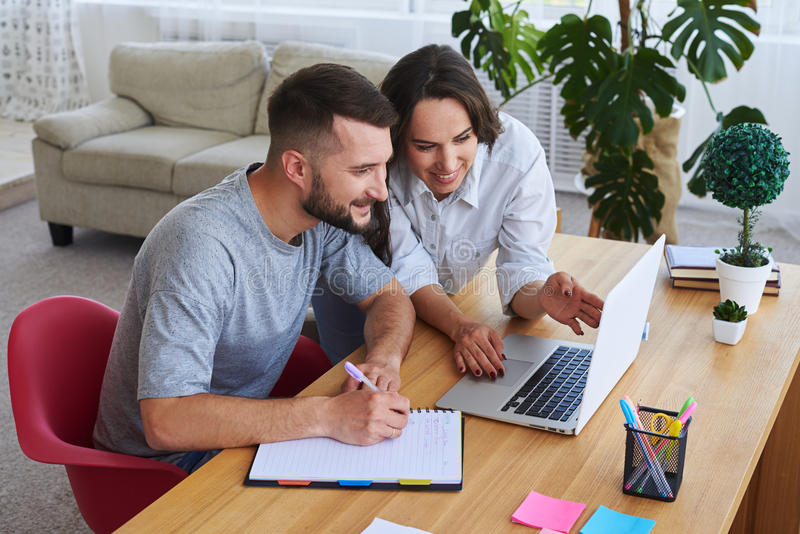 Husband writing in notebook while wife showing something to him. High angle of husband writing in notebook while wife showing something to him in laptop stock photos