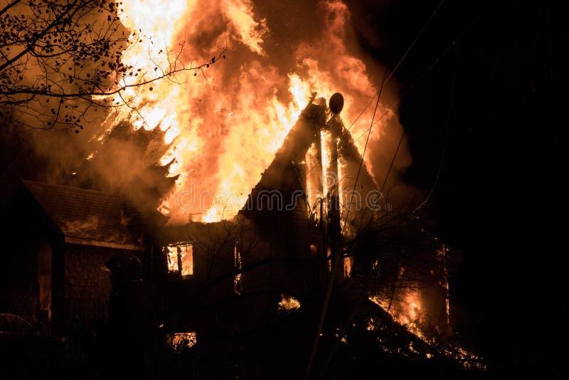Husbrand med den intensiva flamman, överväldigade fullständigt husbrand arkivbild