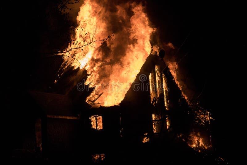 Husbrand med den intensiva flamman, överväldigade fullständigt husbrand royaltyfri bild