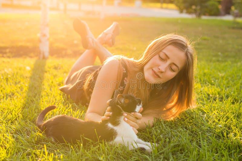 Husdjur och ägarebegrepp - härlig flicka som spelar med en katt i gräset arkivbilder