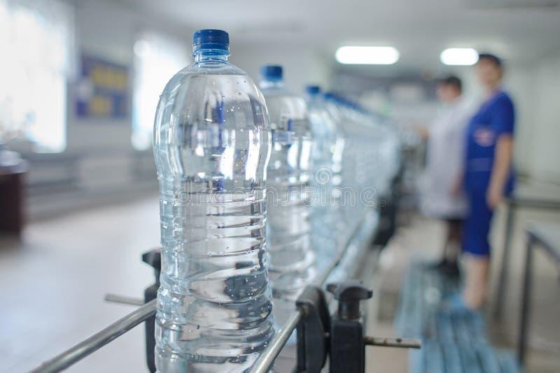 Husdjurflaska med naturlig vattentillverkning slapp fokus royaltyfri foto