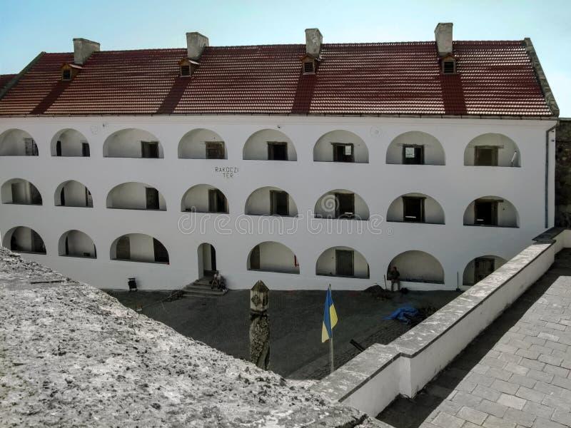 Huset av den Palanok slotten med vita väggar, välvda fönster och ett rött belagt med tegel tak - bästa sikt arkivbilder