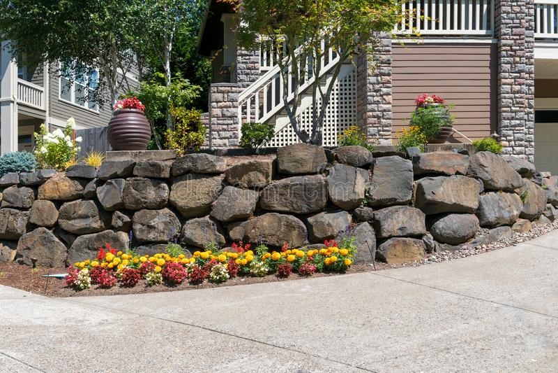 Huset Front Yard Landscaping med vaggar den behållande väggen royaltyfri foto