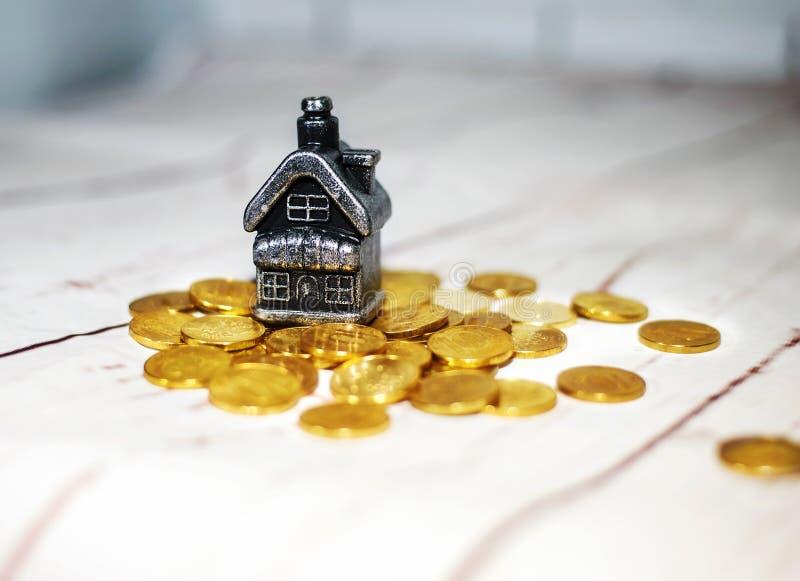 Huset står på en hög av mynt, begreppet av kontanta besparingar royaltyfria foton