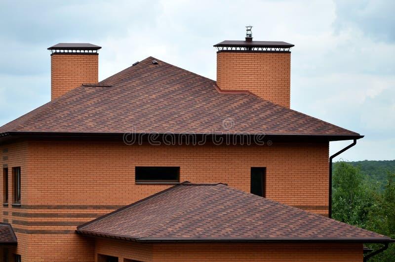 Huset utrustas med högkvalitativt taklägga av singelbitumentegelplattor Ett bra exempel av perfekt taklägga Taket är reliaen arkivfoton