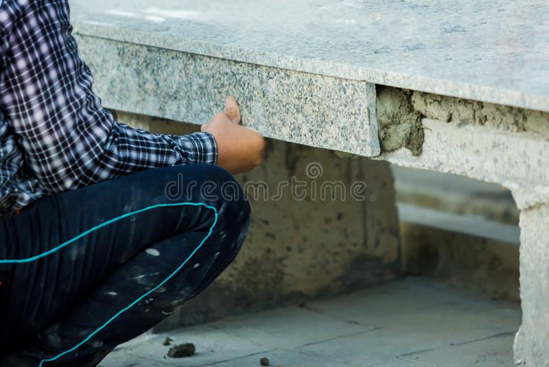 Husförbättring, renovering, arbetare för konstruktionsbransch som installerar granitstentegelplattor med cement royaltyfri fotografi