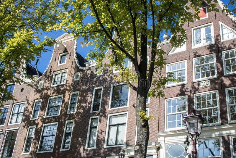 Husfasader i Amsterdam som ses från kanalen arkivbilder