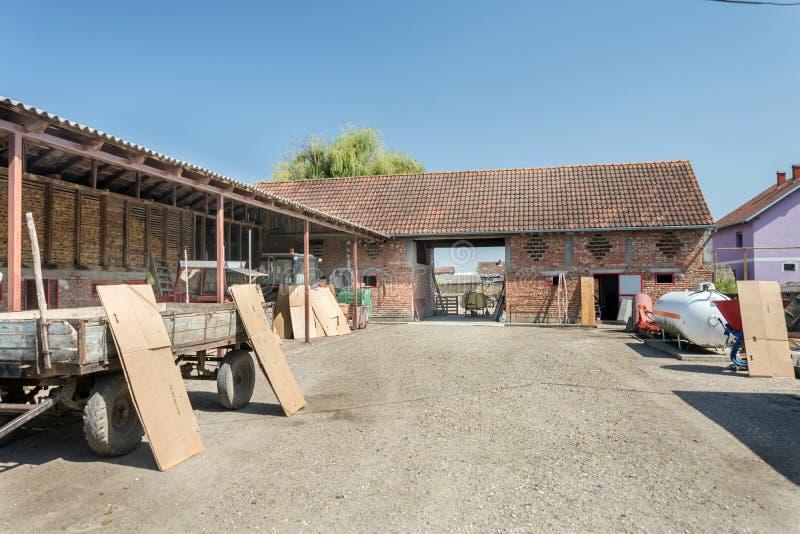 Hushåll i byn med stall och traktorer i gården arkivfoton