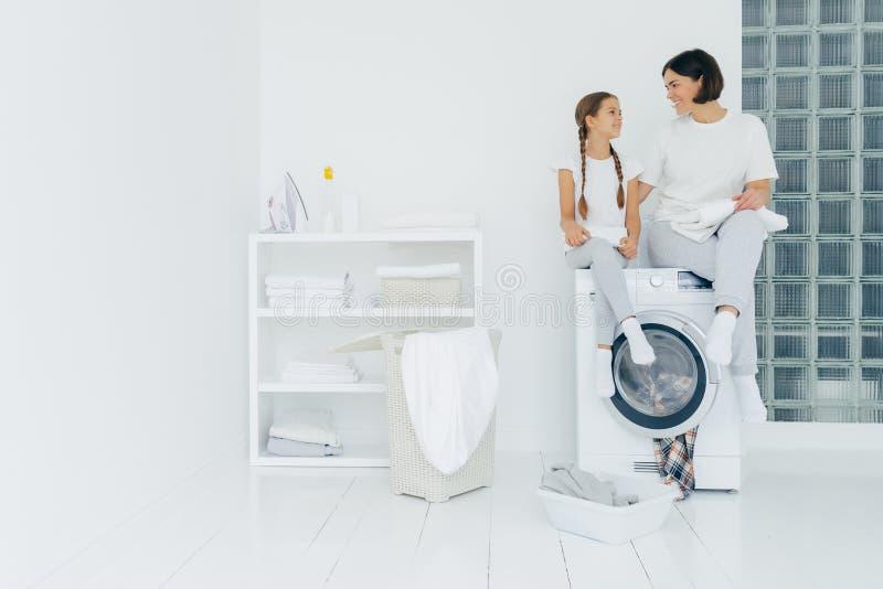 Hushåll och små barn sitter ovanpå tvättmaskinen, håller nytvättade handdukar, tvättar tillsammans och bär vita t-skjortor. royaltyfri fotografi
