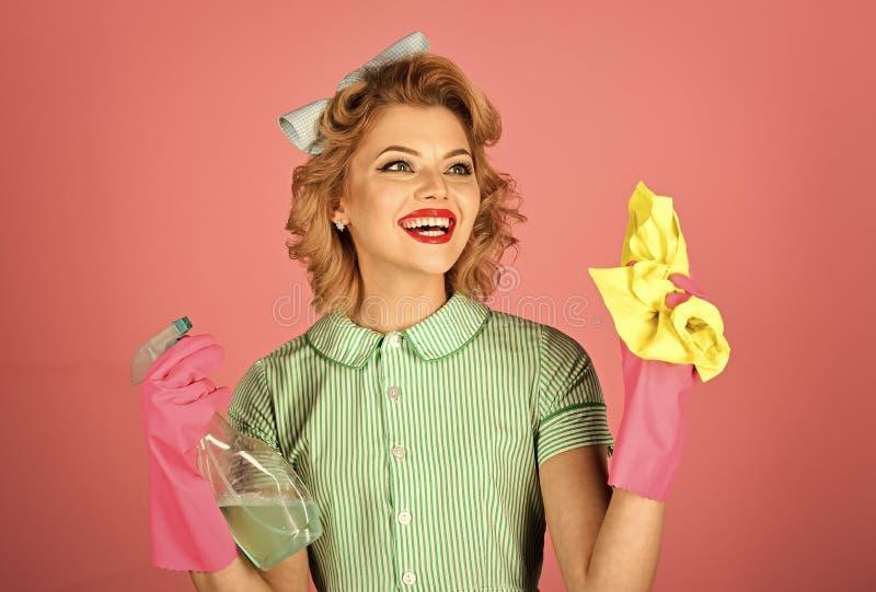 Hushållerska i likformig med ren sprej, dammtrasa royaltyfri fotografi