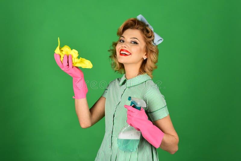 Hushållerska i likformig med ren sprej, dammtrasa royaltyfria foton
