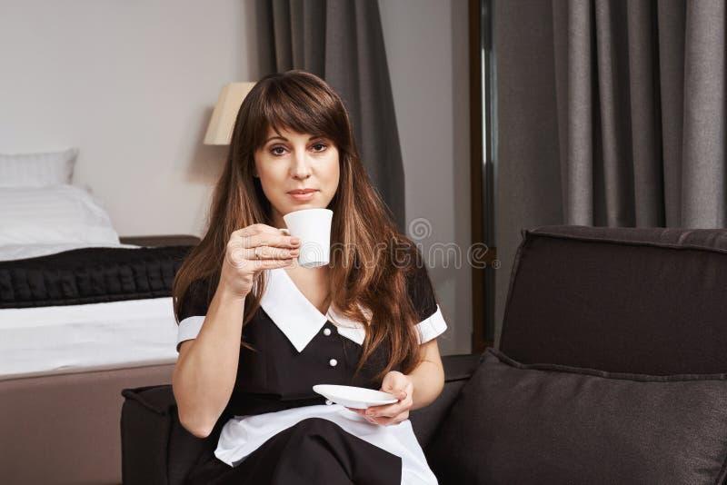 Hushållerska på vakten av renhet Inomhus skott av den lugna och säkra hembiträdet i enhetligt sammanträde på soffa- och innehavko royaltyfria bilder